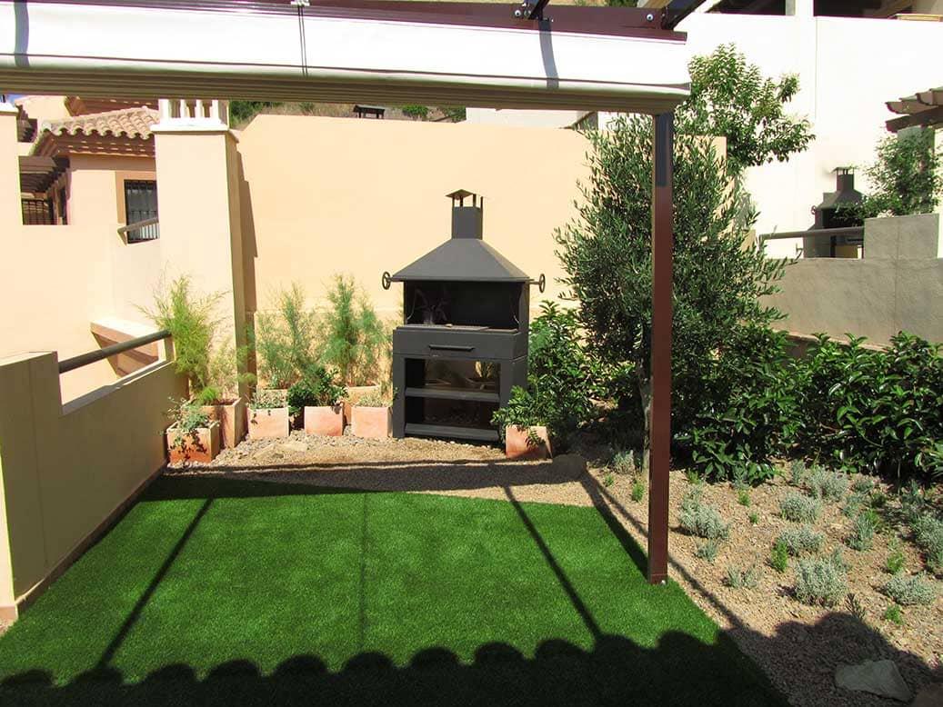 La barbacoa sobre grava ornamental. Se aprovechó el único espacio real de arriate para plantar un olivo y aromáticas.