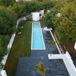 Vista de la piscina rematada por el doble muro que esconde la ducha y la canasta de basquet. Al fondo se puede observar el acceso secundario