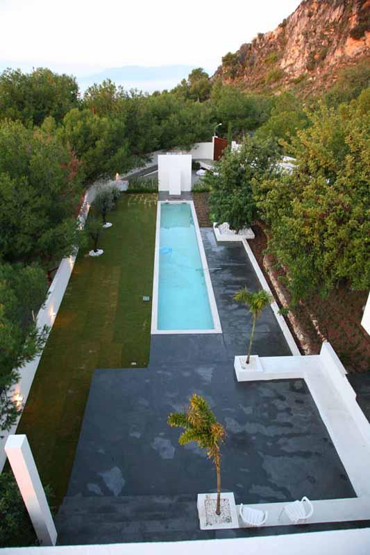 Vista de la piscina rematada por el doble muro que esconde la ducha y la canasta de basquet. Al fondo se puede observar el acceso secundario.