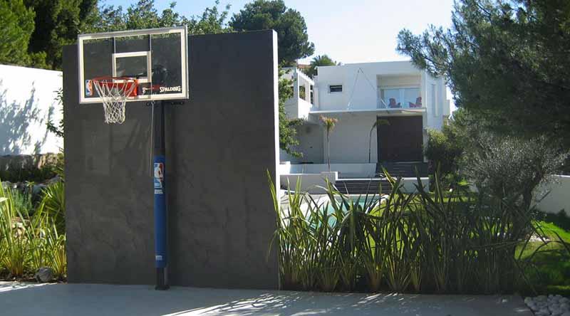 Canasta de básquet detrás del muro que remata la piscina.