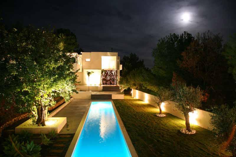 Vista de la casa y la piscina iluminada.