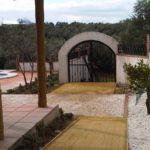 Vista del porche y el acceso norte. El pavimento del camino es de terrazo ecologico y los laterales, con canto rodado, ocultan los drenes
