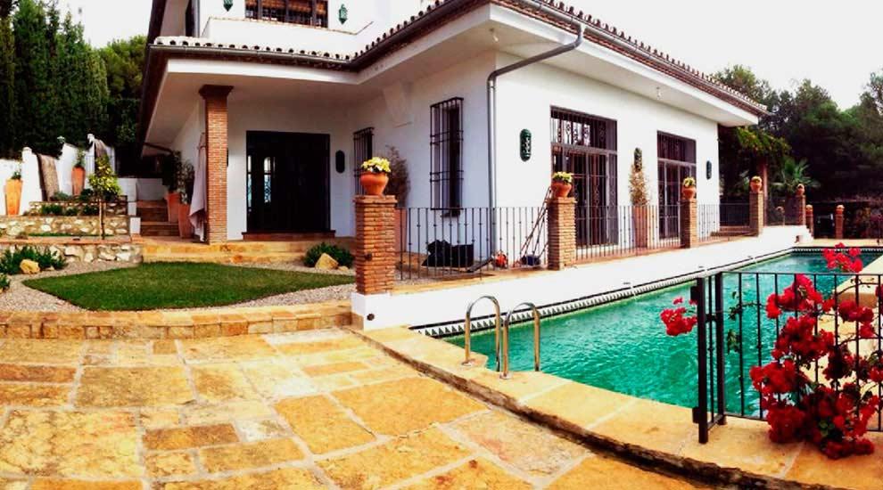 Fachada Villa Palmeras. Scina, con pequeña pradera y huerto.
