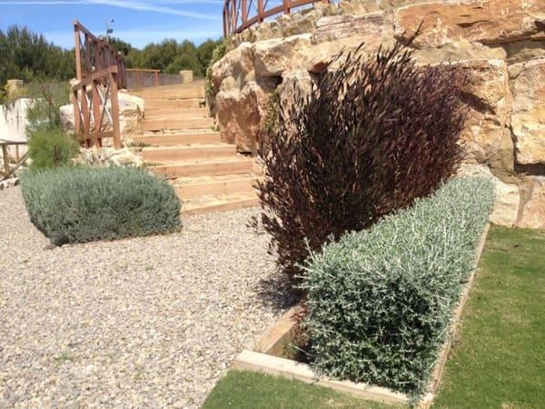 Jardín inferior y escalera de traviesas de madera que comunica con la pradera superior