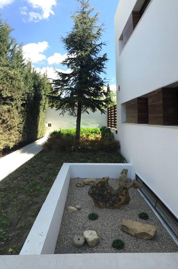 Jardineras, patio inglés y fuente.