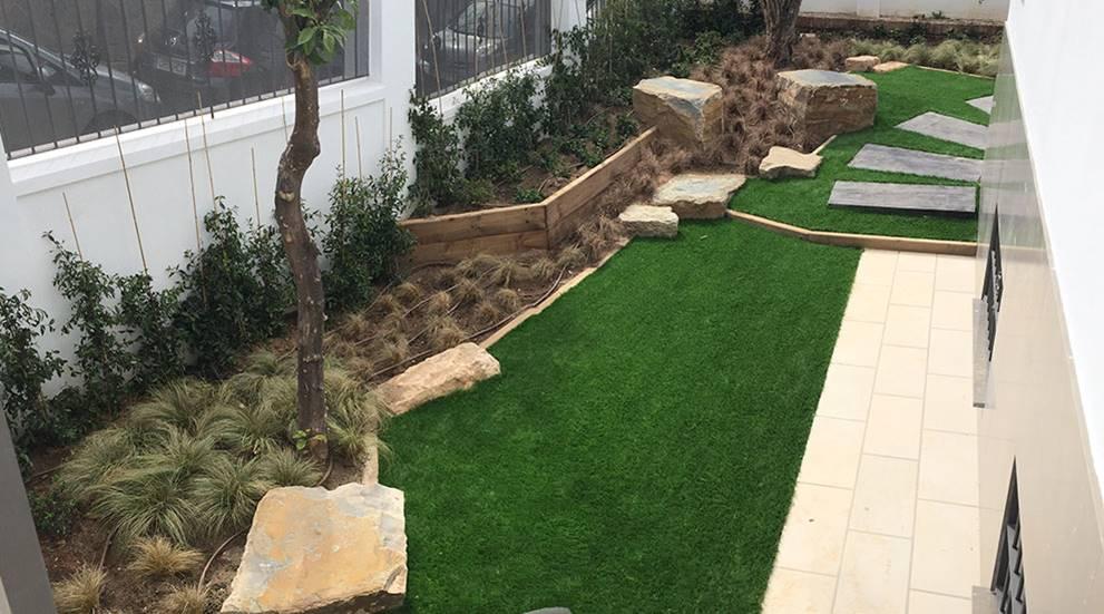 Jardín de entrada con césped artificial, bordillo de madera y rocas.
