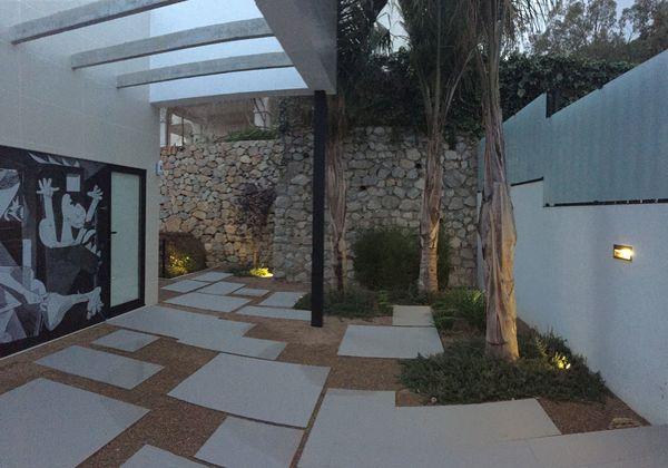 Patio de acceso con huellas de piedra y áridos.