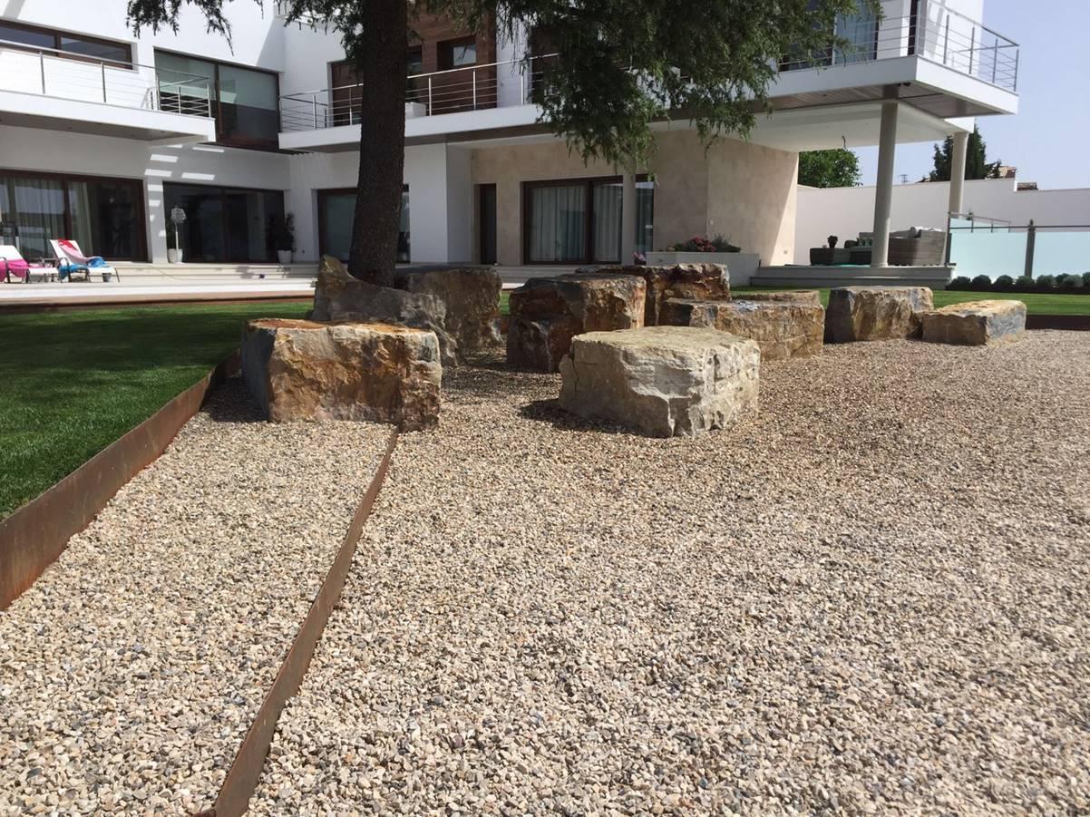 Escalones de acero corten y rocas acentuando el ciprés.