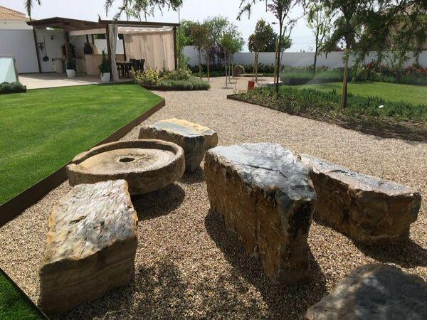 Vista de la pérgola desde el jardín intermedio de grava, el cual conecta las praderas que se encuentran a diferentes niveles.