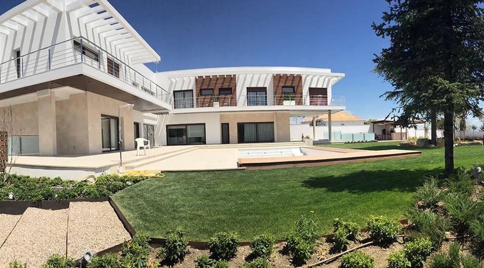 Vista de la pradera superior con la piscina y las escaleras de acero corten,.